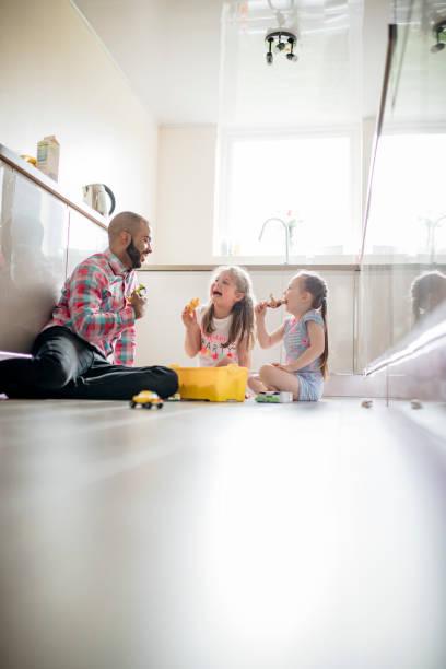 vater und seine töchter spielen auf dem küchenboden - liebeskummer englisch stock-fotos und bilder