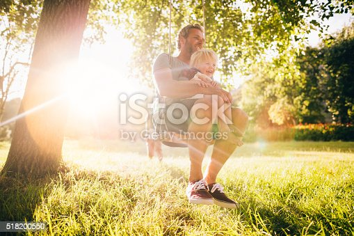 istock Father and his laughing son enjoy summer sunset on swing 518200550