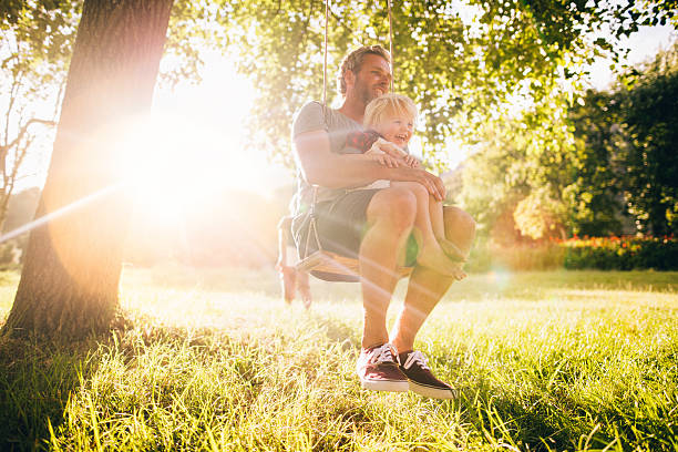 Father and his laughing son enjoy summer sunset on swing stock photo