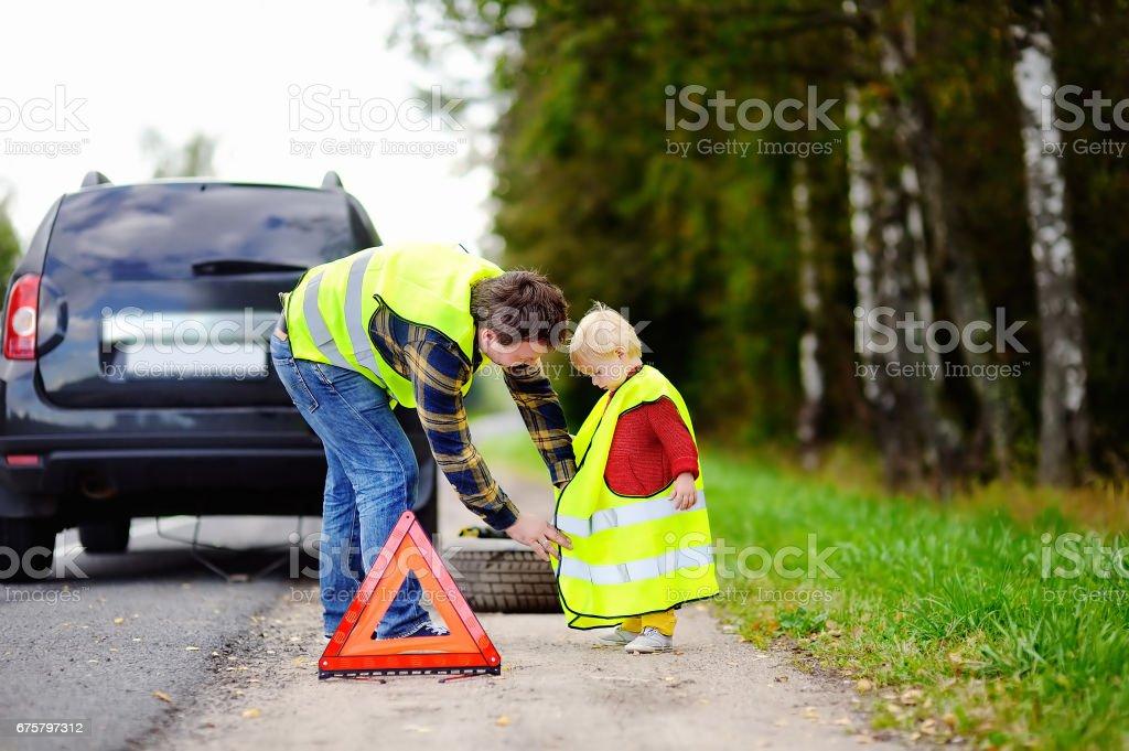 Padre y su pequeño hijo reparación de coches y cambio de rueda - foto de stock