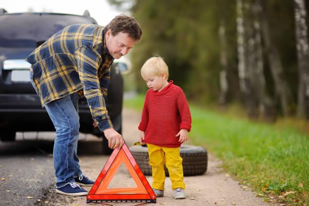 Padre y su pequeño hijo reparar coches y cambiando rueda juntos en el día de verano. - foto de stock