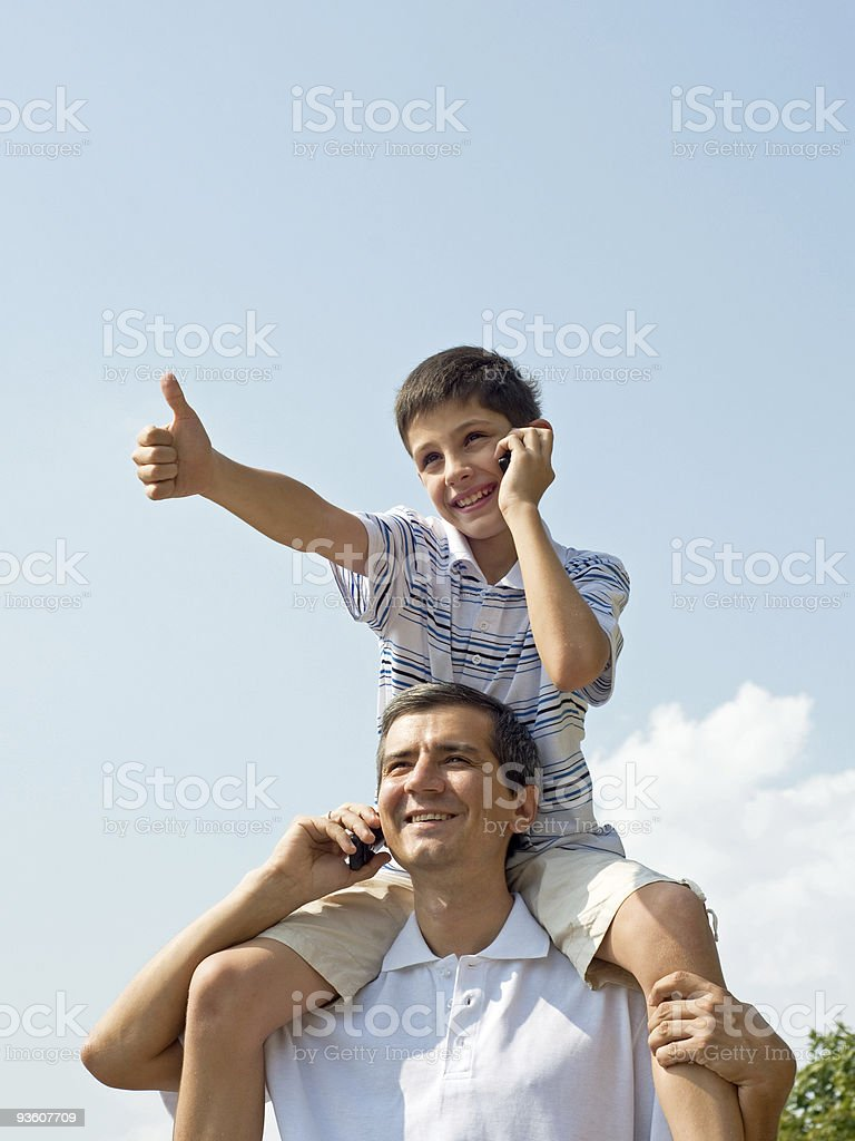 Father and his son are speaking over mobiles royalty-free stock photo