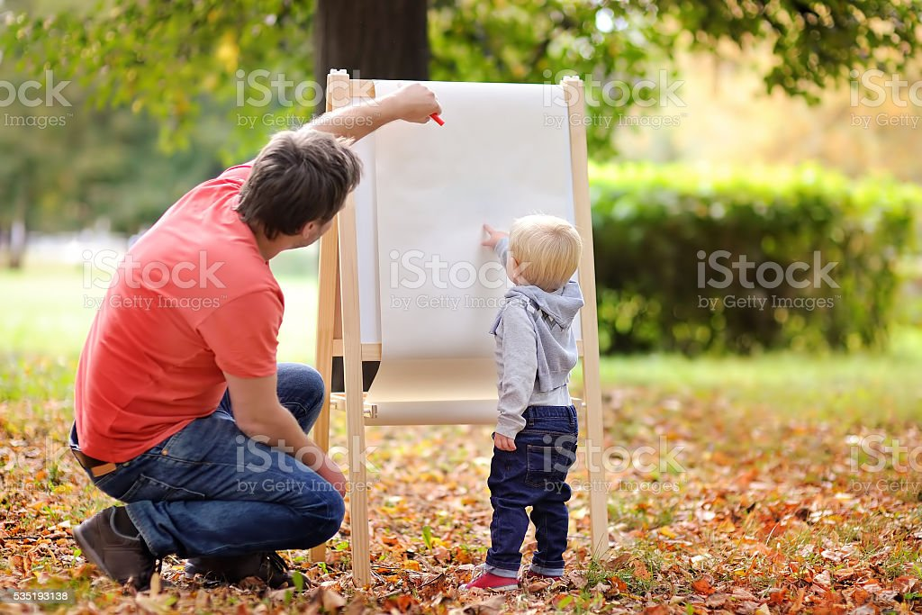 Father and his son drawing on white paper stock photo