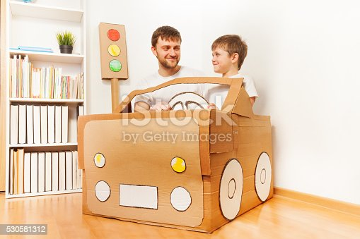496487362 istock photo Father and his son driving handmade cardboard car 530581312