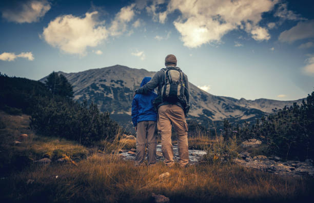 Father and his son hiking in mountains at sunset stock photo