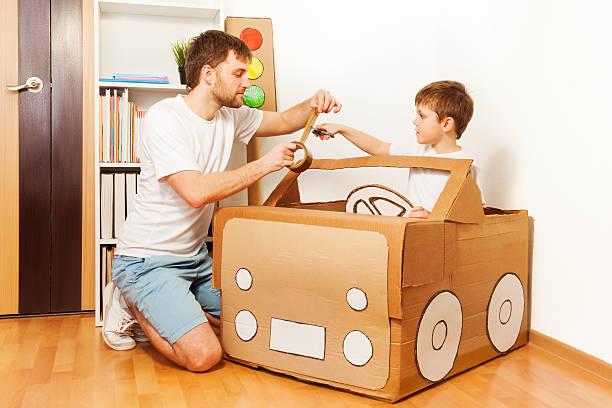 vater mit seinem sohn, spielzeugauto von pappkarton - bastelkarton stock-fotos und bilder