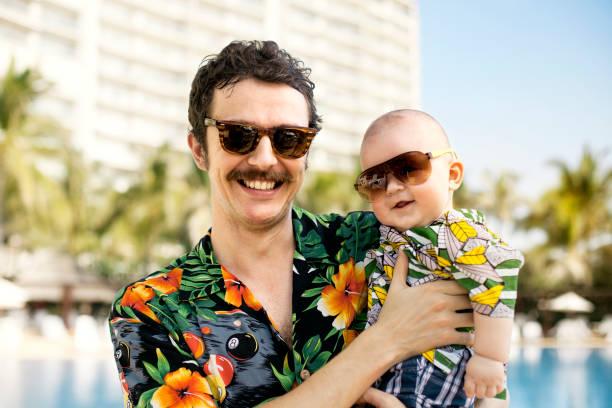 vater und seinem sohn mit hawaian shirts - papa humor stock-fotos und bilder
