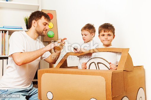 942256562istockphoto Father and his sons making toy car of cardboard 530579628