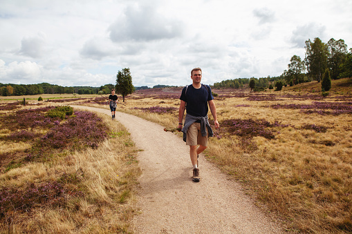 Father and his teenage son in shorts and t-shirts walking on the grassland in a nature reserve in Luneburger Heath among the heather plants on their hiking trip - being together, being active and healthy.