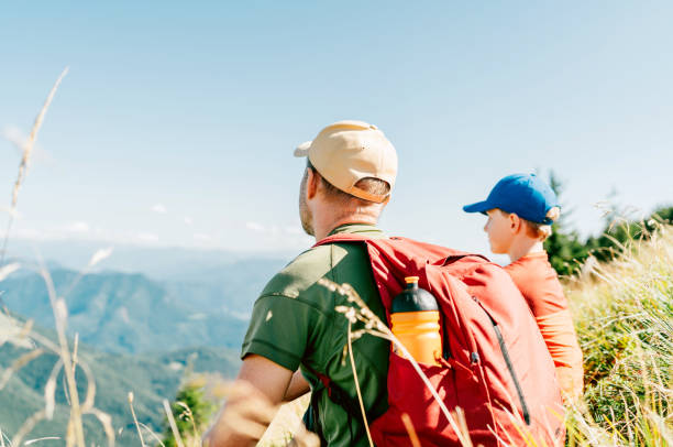Padre y su hijo adolescente sentados en el césped y disfrutando del paisaje de montaña durante su fin de semana caminando. - foto de stock