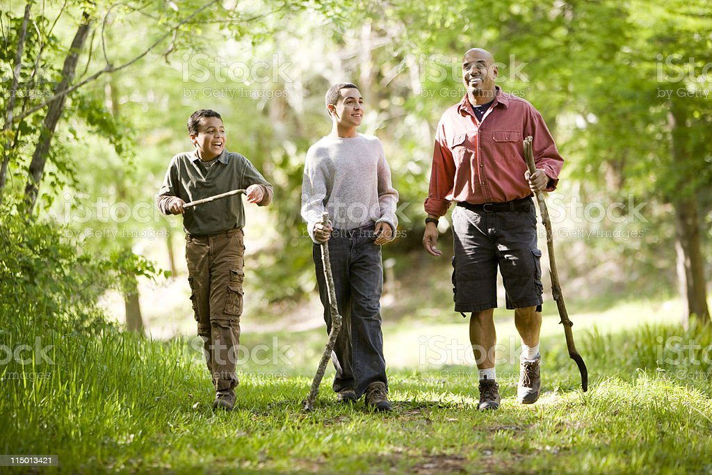 A father and his two sons hike through a forest stock photo