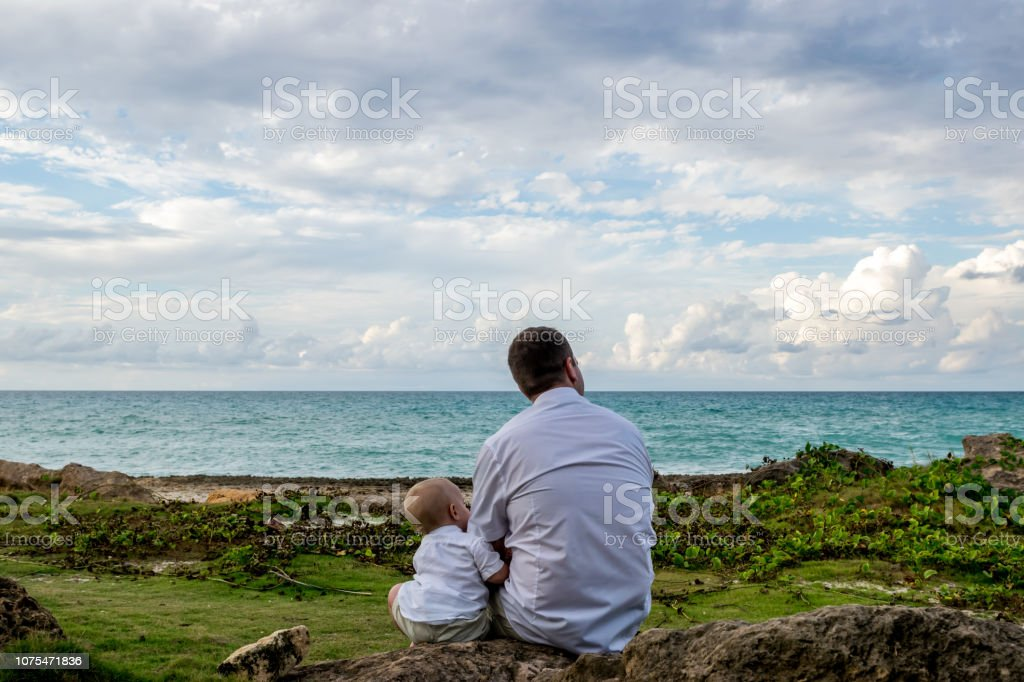 A father and his young son in a wedding celebration stock photo