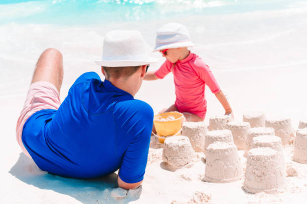 Vater und Kind machen Sandburg am tropischen Strand. Familie spielt mit Strandspielzeug – Foto