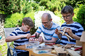 istock Father and kids crafting fun stuff using pieces of wood 1312863274