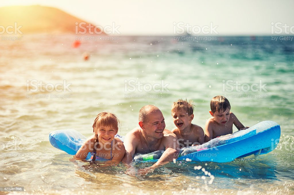Father and kids having fun in sea on air bed stock photo