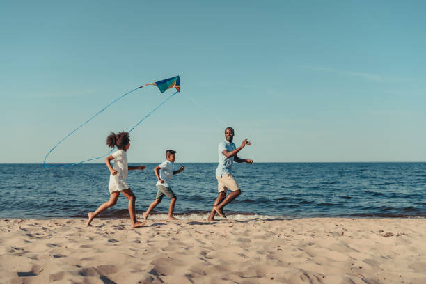 father and kids playing with kite on beach stock photo