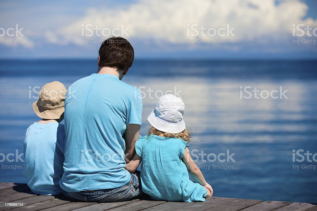 Father and kids sitting on wooden dock royalty-free stock photo