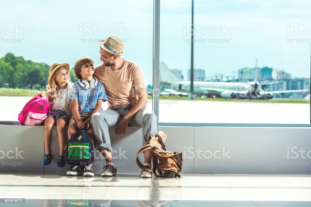 father and kids waiting for boarding stock photo