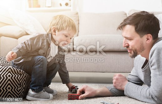 496487362istockphoto Father and little boy playing with toys 1150974677