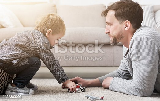 496487362istockphoto Father and little boy playing with toys 1152383099