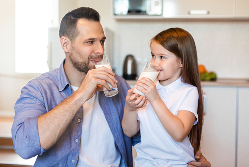 Breakfast With Dad. Father And Little Daughter Drinking Milk Sitting In Kitchen At Home