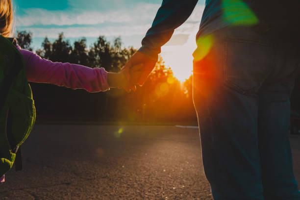 Vater und kleine Tochter gehen bei Sonnenuntergang zur Schule – Foto
