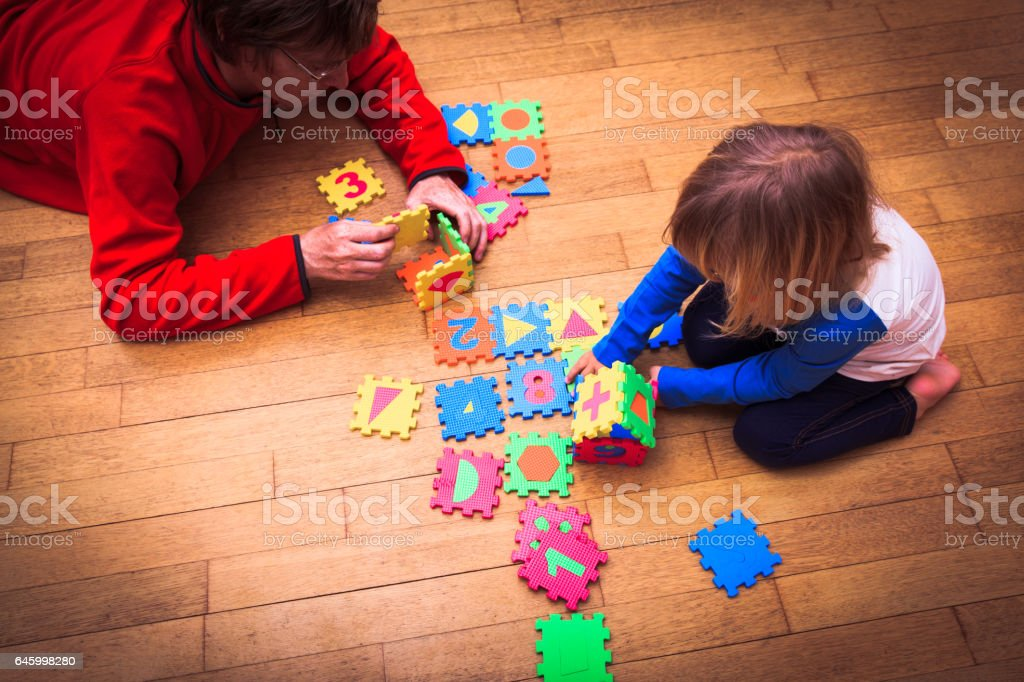 father and little daughter playing with puzzle, early education stock photo