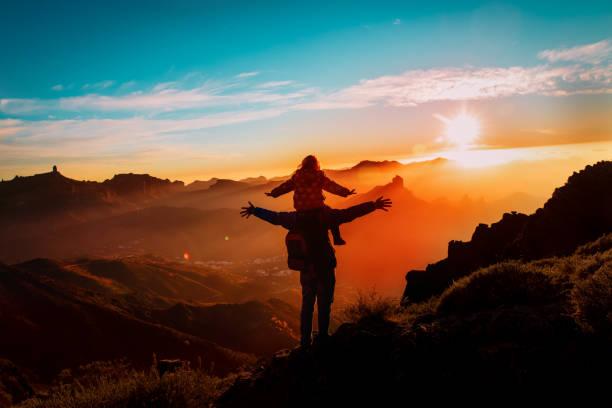 Vater und kleine Tochter reisen bei Sonnenuntergang in die Berge – Foto