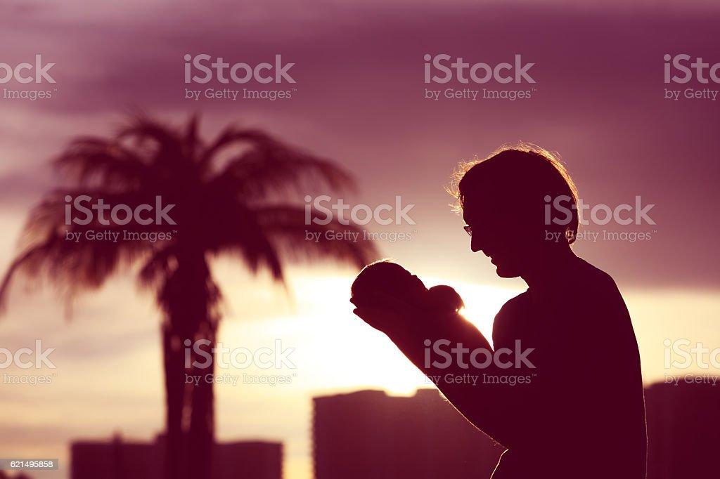 Petite fille de père et nouveau-né silhouettes au coucher de soleil photo libre de droits