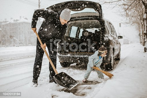 Father and little son cleaning snow around car