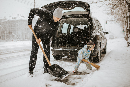 istock Father and little son cleaning snow around car 1042013194
