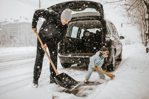 父親和小兒子在汽車周圍清掃雪 - 鏟 個照片及圖片檔