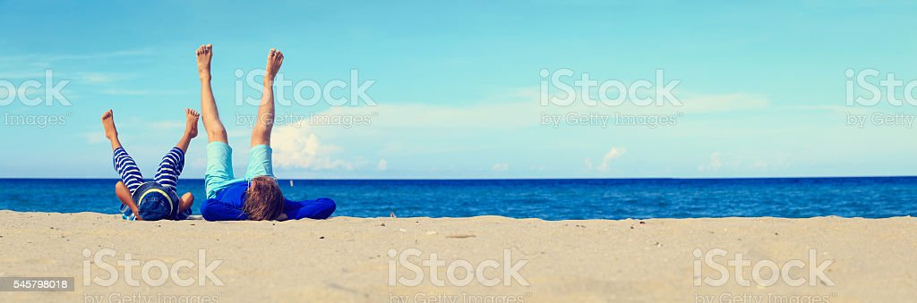 father and little son play on beach stock photo