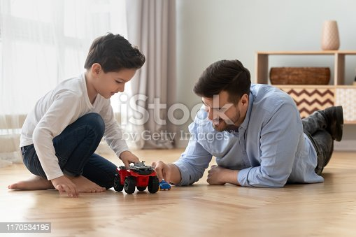 540396126istockphoto Father and little son playing toy cars on warm floor 1170534195