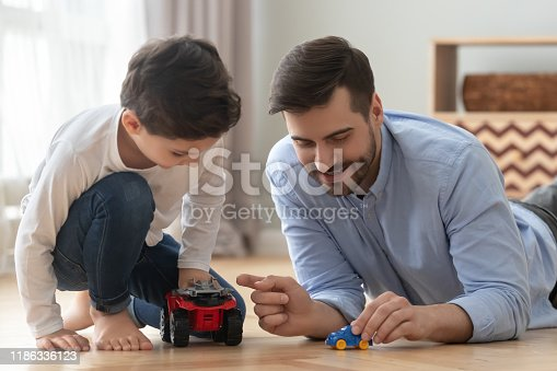 942256562istockphoto Father and little son racing playing toy cars at home 1186336123