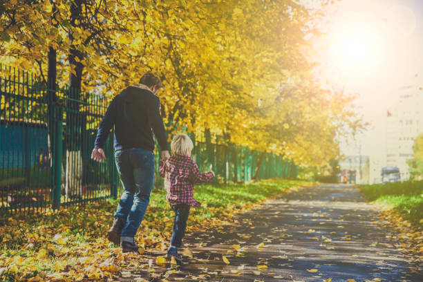 Father and Little Son Walking Outdoors in Autumn stock photo