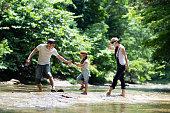 父と母と娘が川で遊ぶ