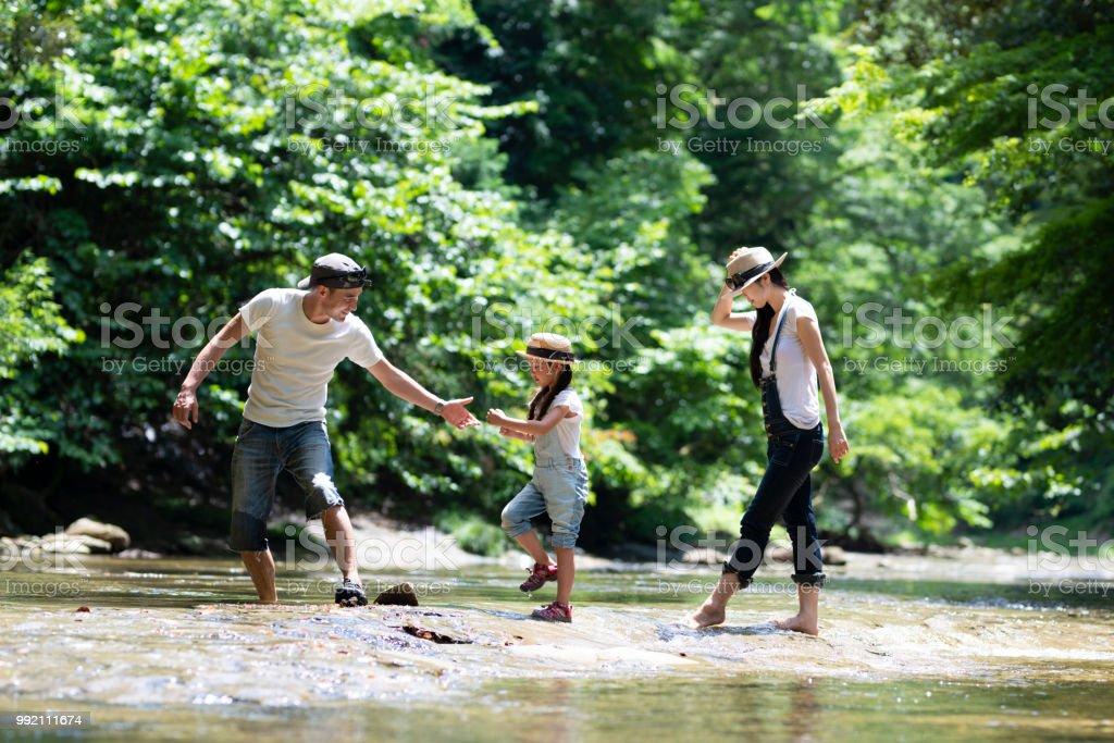 父と母と娘が川で遊ぶ ストックフォト