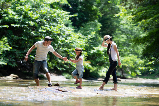 Father and mother and daughter play in the river stock photo