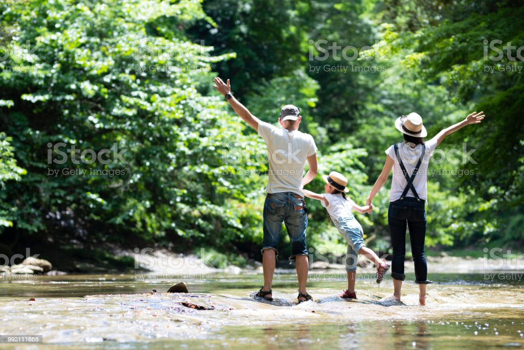 父と母と娘が川で遊ぶ - 30代の女性のロイヤリティフリーストックフォト