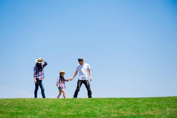 牧草地で遊んでいる父と母と娘 - 家族 日本人 ストックフォトと画像