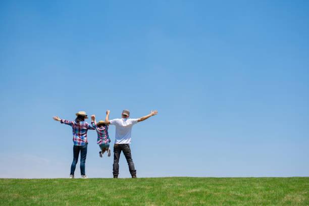 牧草地で遊んでいる父と母と娘 - ライフスタイル ストックフォトと画像