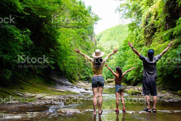 Photo of Father and mother and daughter playing in the mountain stream