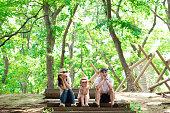 父と母と娘は公園の森に座る