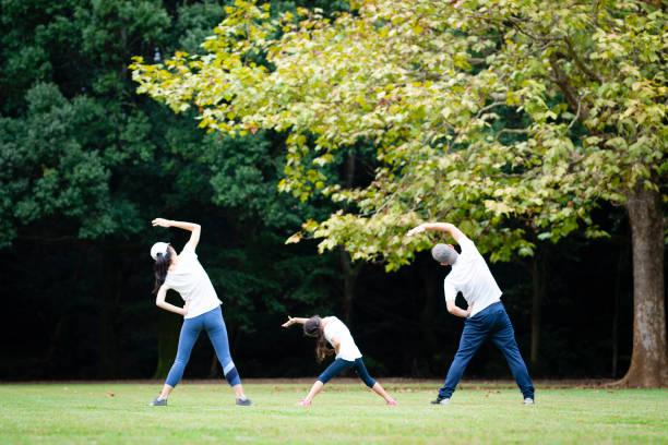 父と母と娘、ストレッチを - 体操競技 ストックフォトと画像