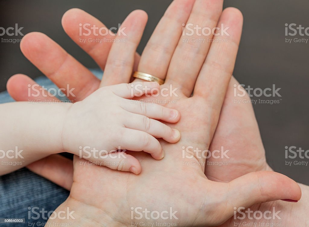 Father and mother holding child's hand stock photo