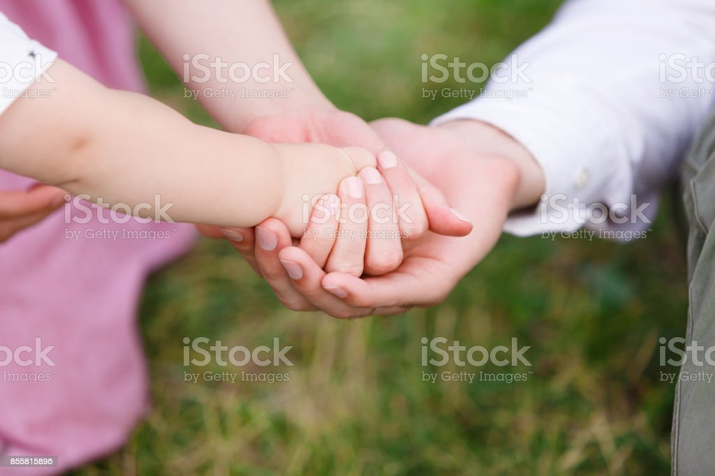 Father and mother holding their baby hand. Child hand closeup into...