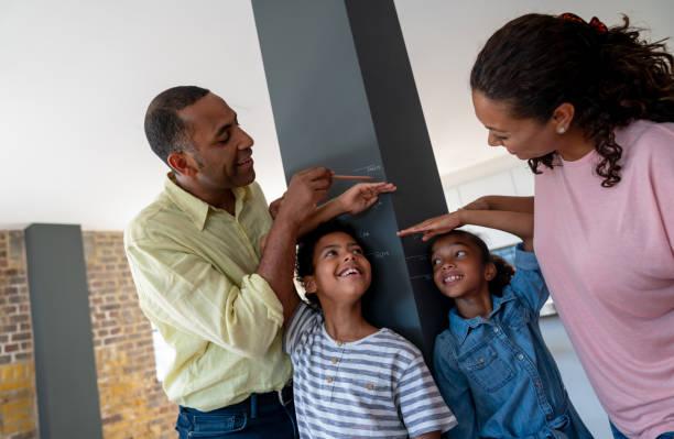 Vater und Mutter, die ihre Kinder zu Hause messen – Foto