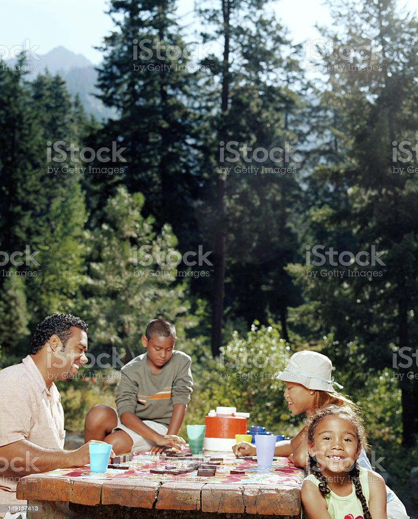 Father and mother sitting with son and daughter (6-11) at picnic stock photo