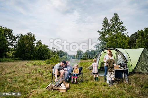 Mid adult parents spending weekend time with their young children on camping trip in woodland area.